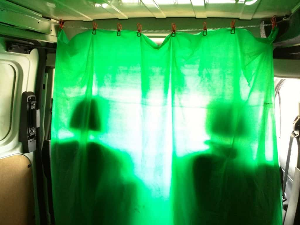 Camping clothesline and plastic tablecloth curtain in van