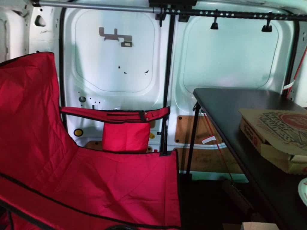 Folding table, camping chair, and garment bar inside van